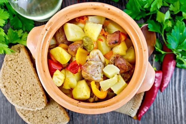 Assado com frango, batata, abóbora e pimentão em uma panela de barro em um guardanapo de serapilheira, pão e salsa em um fundo de tábuas de madeira em cima
