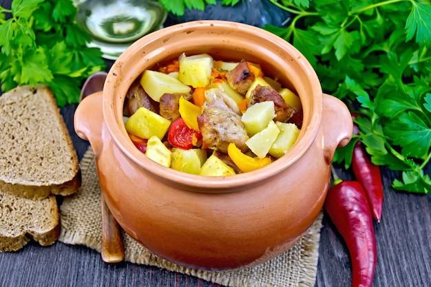 Assado com frango, batata, abóbora e pimentão em uma panela de barro em um guardanapo de serapilheira, pão e salsa sobre um fundo de tábua de madeira