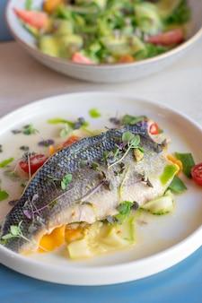 Assado cozido metade do peixe decorado com tomate cereja rodelas de pepino e microgreen no prato