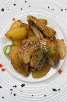 Assado de pintada com batatas, com ervas verdes, colocadas em um prato branco