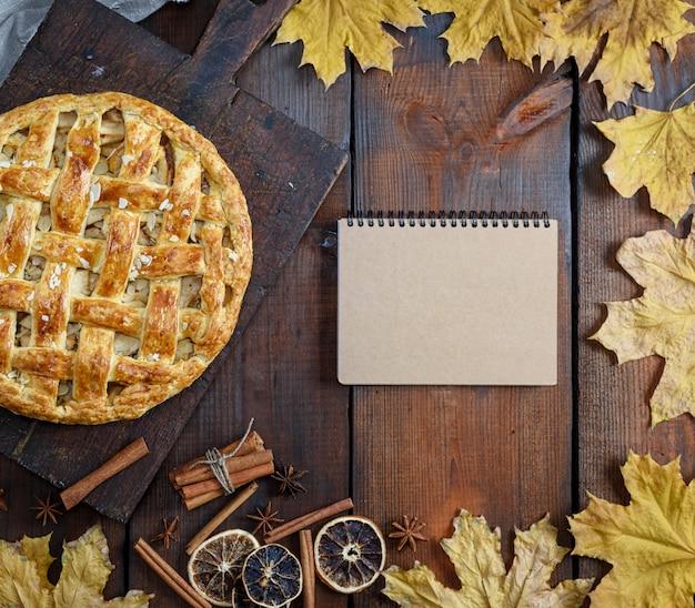 Assado inteiro torta de maçã redonda em uma placa de madeira marrom