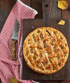 Assado inteiro torta de maçã redonda em uma placa marrom velha retangular