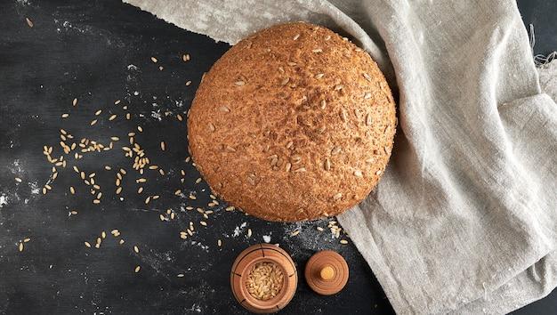 Assado pão de centeio redondo com sementes de girassol em um guardanapo de tecido bege, fundo de madeira
