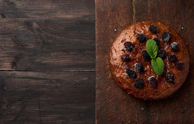 Assado redondo bolo de biscoito com nozes e frutas coberto, br de madeira