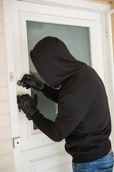 Assaltante quebrando abrir a porta