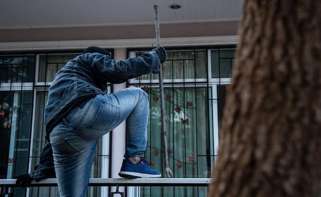 Assaltante roubo ou roubo. escalando a casa