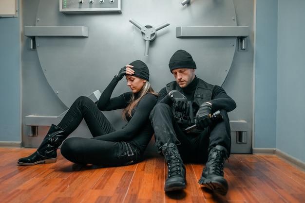 Assalto a banco, assaltantes masculinos e femininos em uniforme preto tentando quebrar a fechadura do cofre. profissão criminosa, conceito de roubo