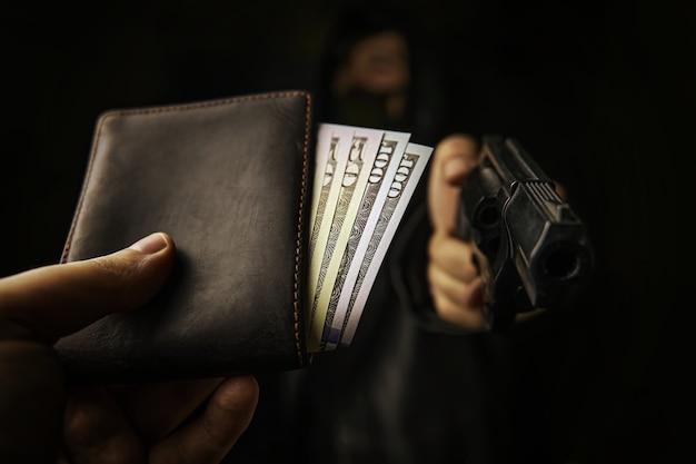 Assalto à mão armada a homem desarmado. a mão de homem estende carteira de dinheiro para ladrão com arma de cem ...
