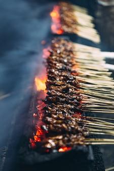 Assar carne, frango e carneiro satays com carvão, fogo e fumaça.