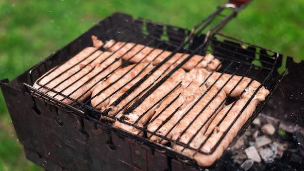 Assar carnes na grelha na natureza