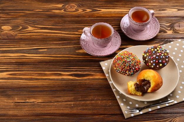 Assar com chá e chocolate na mesa. duas xícaras de chá com cupcakes e chocolate com um pó multicolorido na mesa.