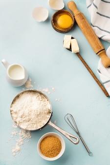 Assar com ingredientes de farinha, ovos, açúcar, manteiga, canela, estrela de anis e utensílios de cozinha na mesa rústica azul. foco seletivo. vista do topo.