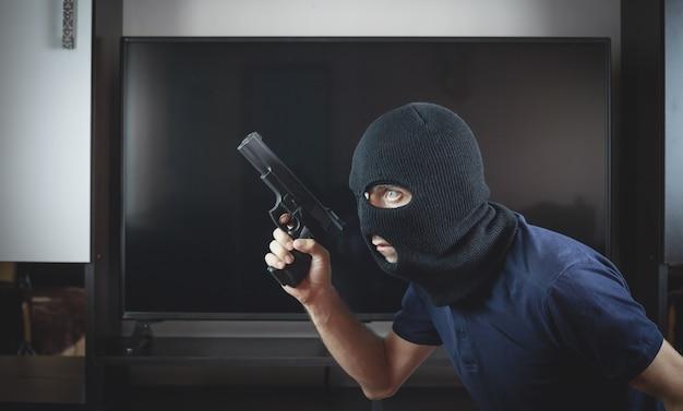 Assassino com uma pistola e uma balaclava preta em casa.