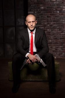 Assassino de terno e gravata vermelha segurando a pistola