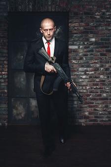 Assassino de terno e gravata vermelha segurando uma metralhadora nas mãos.