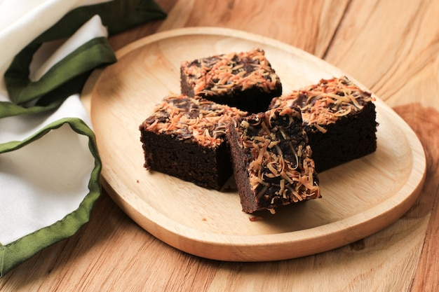 Asse brownie com queijo ralado por cima (brownies keju), bolo de chocolate caseiro fresco cozido na mesa de madeira. fechar-se.