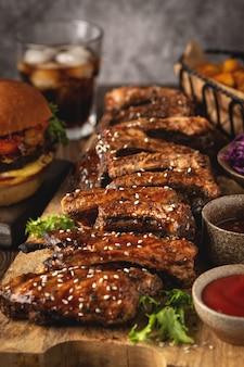 Asse costeletas de porco em uma placa de madeira, fatias de batata, hambúrguer e coca-cola de vidro, sause. comida rápida. fechar-se.