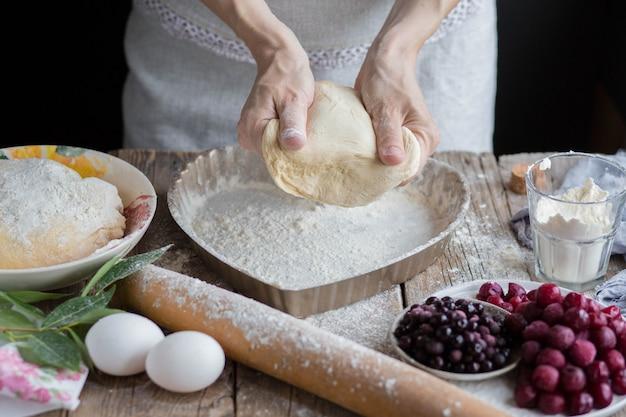 Asse um bolo de frutas em forma de coração. as mãos espalham a massa sobre o bolo. cozinhando