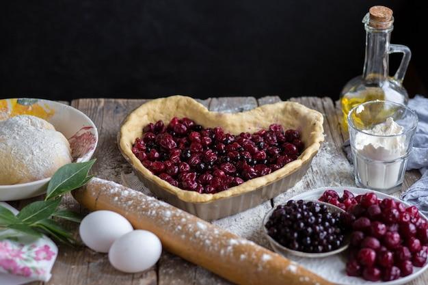 Asse um bolo de frutas em forma de coração. delicioso bolo caseiro faça você mesmo. cozinhando.