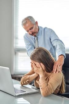 Assédio com um chefe tocando o braço em sua secretária que está sentada em seu local de trabalho no escritório