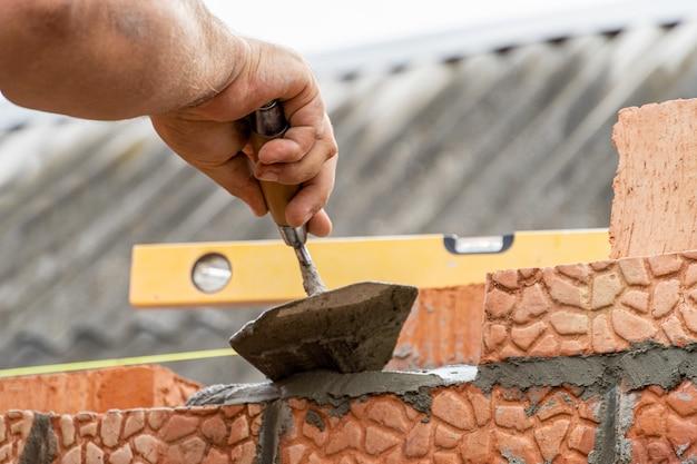 Assentamento de tijolos com ferramentas manuais durante o close up da construção