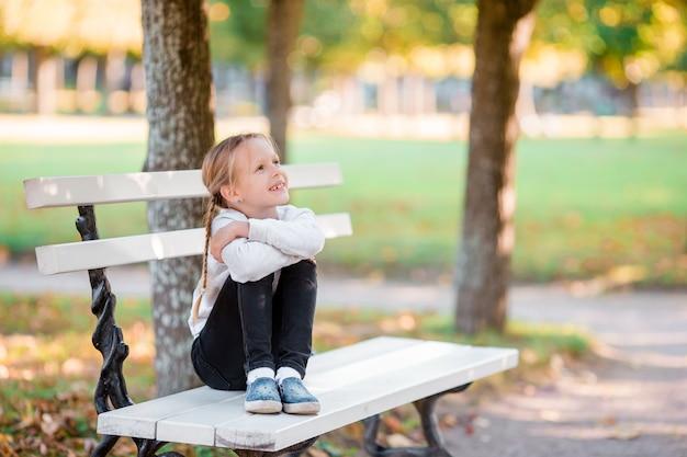 Assento bonito da criança perdido no pensamento no dia bonito do outono fora. menina no banco em queda