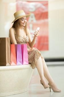 Assento da rapariga com sacos de compras, enquanto observa o celular