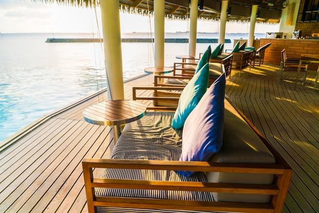 Assento das férias na ilha tropical de maldivas e na beleza do mar com os recifes de corais.