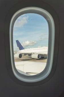 Assento de avião e janela dentro de uma aeronave