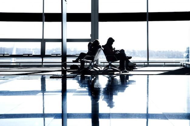 Assento de janela grande descansando preto branco silhueta sol passageiros esperando portão terminal aeroporto