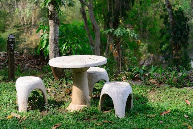 Assento de jardim de pedra ou mesa e bancos de pedra no jardim.