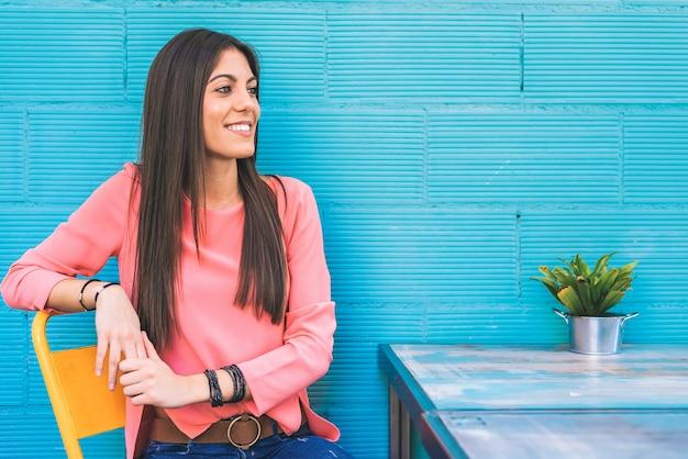 Assento feliz da jovem mulher em um restaurante