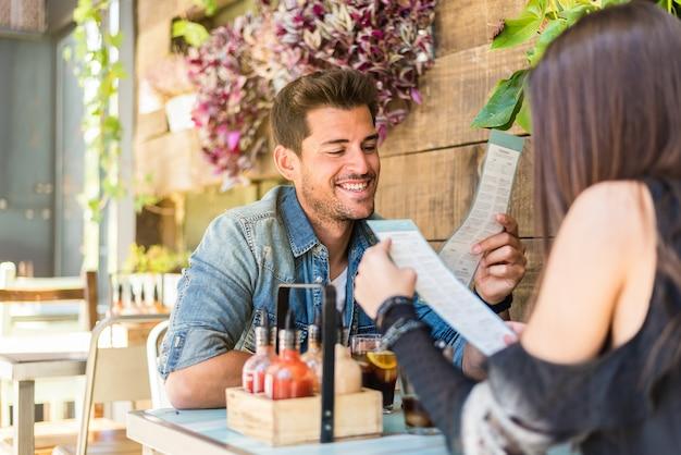 Assento feliz jovem casal em um restaurante, olhando para o menu