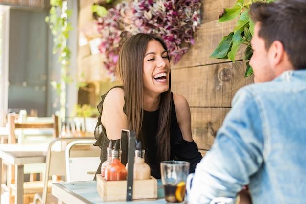 Assento feliz jovem casal em um restaurante