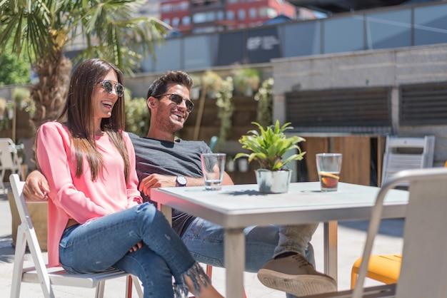 Assento feliz jovem casal relaxado em um restaurante com terraço