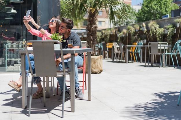 Assento feliz jovem casal relaxado em um terraço de restaurante tomando uma selfie com smartphone