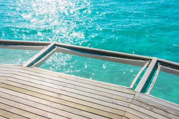 Assento líquido das férias na ilha tropical de maldivas e na beleza do mar com os recifes de corais.