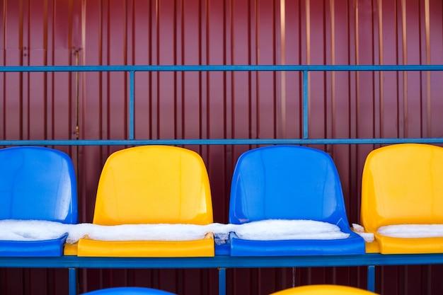 Assentos coloridos cobertos de neve no estádio nevado do inverno. tribuna coberta de neve