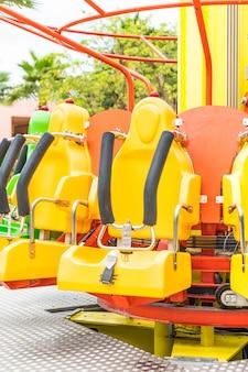 Assentos coloridos da montanha russa no parque de diversões