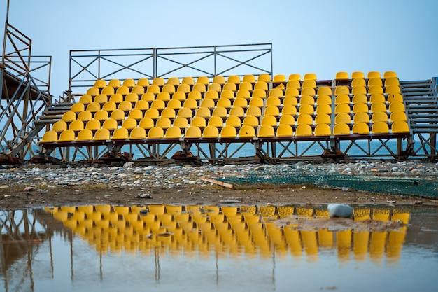 Assentos de plástico amarelo no pódio de um pequeno campo esportivo.