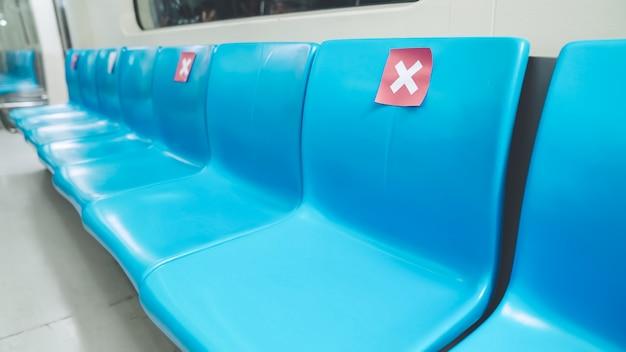 Assentos em metrô público subterrâneo com placas de distanciamento social