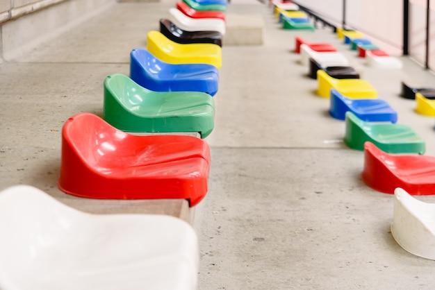 Assentos plásticos vazios coloridos nos suportes de um estádio dos esportes.