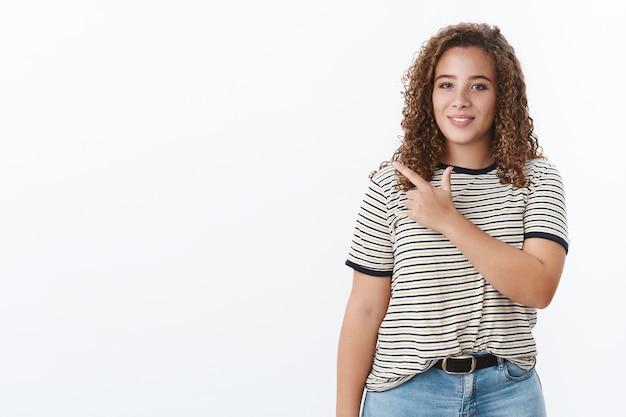 Assertiva, confiante, atraente, gordinha, de cabelos cacheados, apontando o dedo indicador esquerdo para o lado, mostrando o espaço em branco