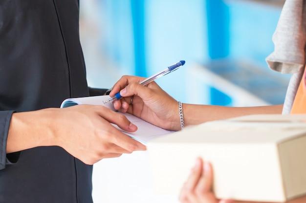 Assinando o recibo do pacote da caixa de entrega em forma de documento, assinar o recibo e segurando o transporte de papelão