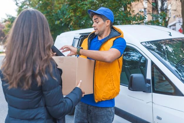 Assinando para pegar o pacote dela. sorrindo, jovem, entrega, homem, segurando, um, caixa papelão, enquanto, beaut