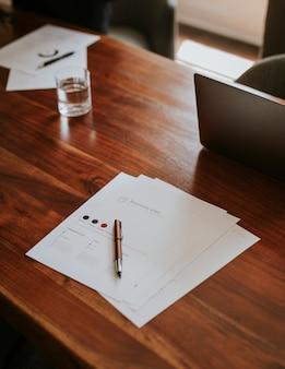 Assinar documentos em um escritório em uma mesa de madeira