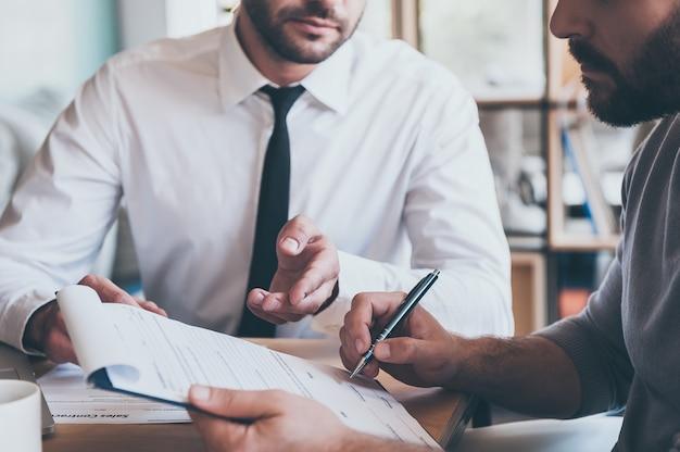 Assinatura de contrato. close de um jovem confiante assinando um documento, enquanto outro homem de camisa e gravata está sentado perto dele e apontando o documento