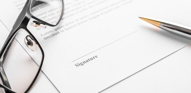 Assinatura de contrato com caneta e óculos
