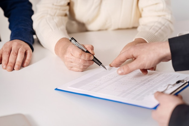 Assinatura de empréstimo hipotecário. casal idoso decidido e atento, sentado em casa, conversando com o corretor de imóveis enquanto assina o documento