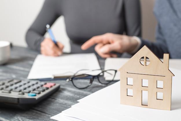Assinatura de um contrato imobiliário entre um corretor de imóveis e um cliente.